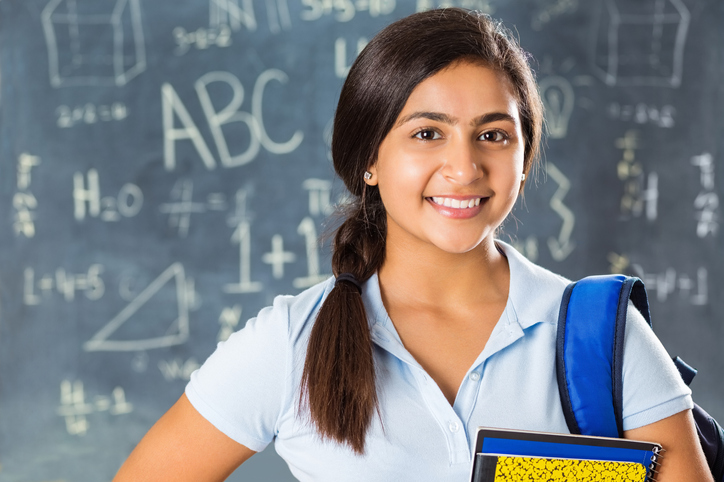 Portrait of pretty Indian high school student in classroom